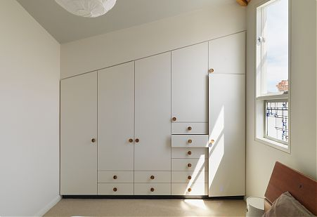 Compact bedroom integrated wardrobe storage.