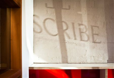 Scribe Publications signage shadow brick wall